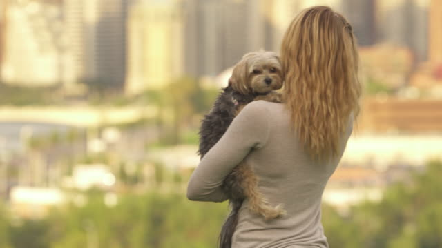 Woman holds dog in urban park, city skyline behind