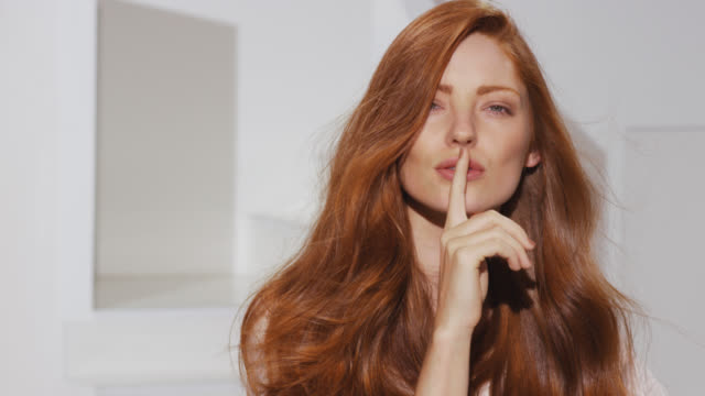 Woman holds her finger to her lips while red hair blows in breeze