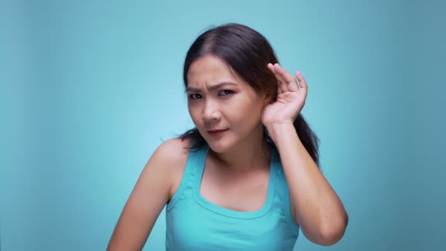 女性は隔離された青い背景 4 k で聴く耳の近くの彼女の手を保持します。 - 盗み聞き点の映像素材/bロール