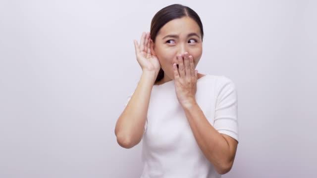 女性は分離ホワイト バック グラウンド 4 k で聴く耳の近くの彼女の手を保持します。 - 盗み聞き点の映像素材/bロール