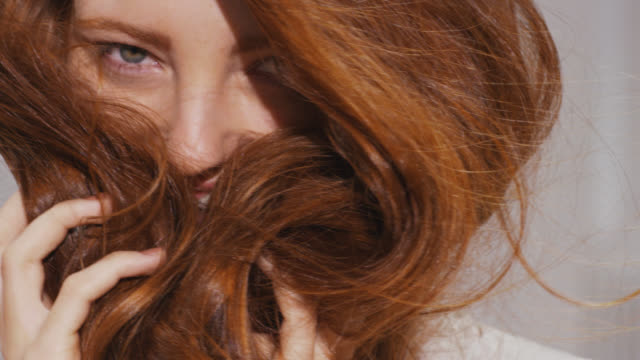 vídeos de stock e filmes b-roll de woman holds her red hair to her face covering her smile - hair