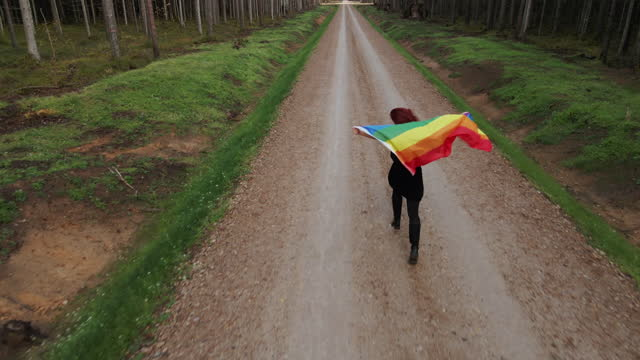 woman holds large rainbow lgbt flag and runs forward in sign of equal rights aerial - rainbow flag stock videos & royalty-free footage