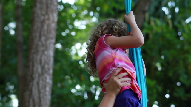 ms tu td ts woman holds little girl as she climbs up fabric hanging from large tropical trees and pulls herself up with her feet / montezuma, puntarenas, costa rica - strength stock videos and b-roll footage