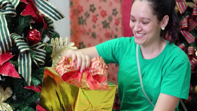 vidéos et rushes de le femme retient le présent sur l'arbre de noël - noeud à boucle