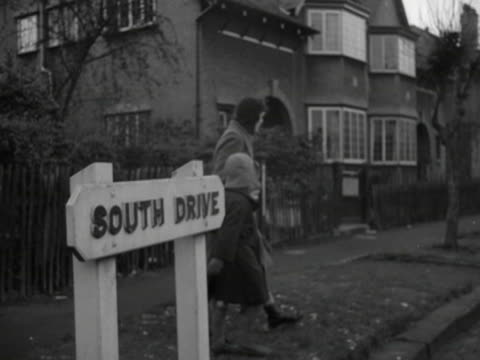 a woman holds the hands of two small children as they cross a quiet suburban street in manchester - bbc archive stock-videos und b-roll-filmmaterial