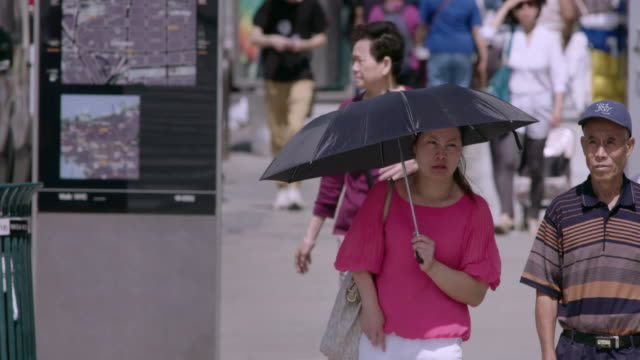 vídeos de stock e filmes b-roll de woman holds umbrella shading herself from sun as she waits at crosswalk. - com sombra