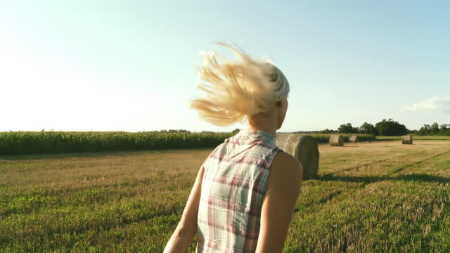 hd steady shot: woman hopping across field of hay bales - hay bale stock videos and b-roll footage