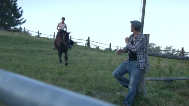 woman horseback riding in rural pasture while man is watching - schiebermütze stock-videos und b-roll-filmmaterial
