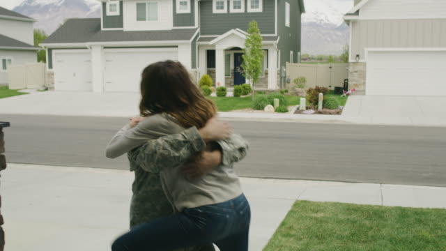 vídeos de stock e filmes b-roll de woman hugging and kissing soldier returning home from duty / lehi, utah, united states - tropa