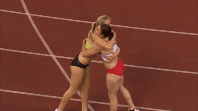 HA MS Woman hugging competitor and waving to crowd after winning track event/ Sheffield, England
