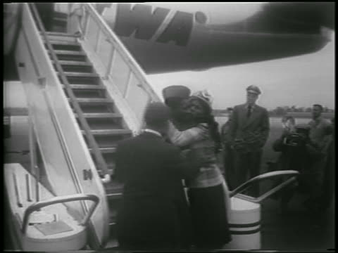 woman hugging soldier on crutches exiting airplane / man pats his back / korean war pow - adult offspring stock videos & royalty-free footage
