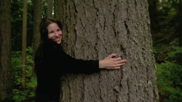 woman hugging tree and smiling - tree hugging stock videos & royalty-free footage