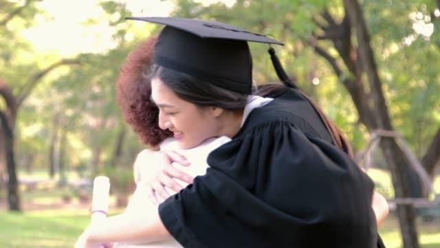 stockvideo's en b-roll-footage met vrouw huging moeder met blij feeling.graduation viering - mortelplank