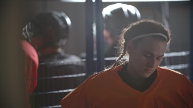 woman ice hockey goaltender putting protective helmet on - スポーツユニフォーム点の映像素材/bロール