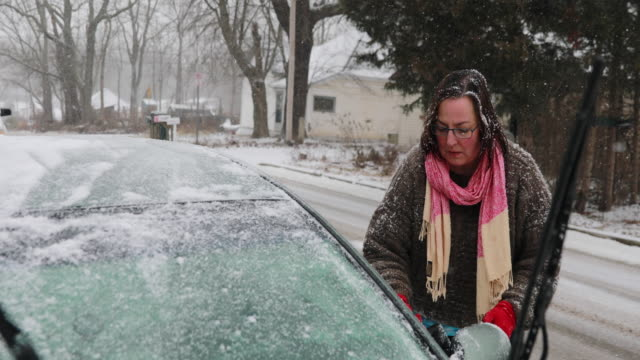 Woman in 50s scraping ice off car in snow