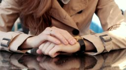Woman in a beige coat eagerly waits at a table in a cafe. Female hands close-up, slow motion.