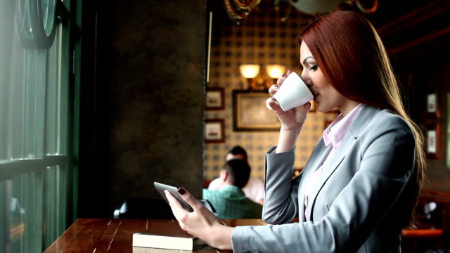 woman in a cafe using tablet and drink coffee - coffee drink stock videos & royalty-free footage