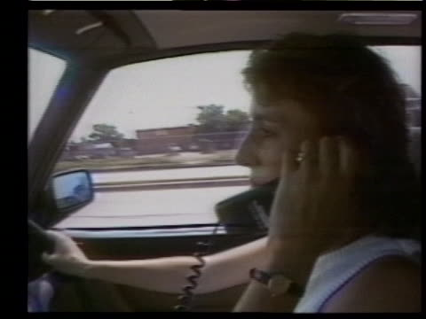 woman in a car on a cellular phone, driving and speaking with a friend in the 1980s - mobile phone stock videos & royalty-free footage