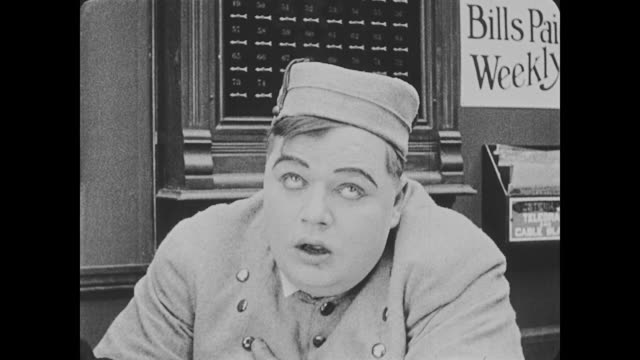 1918 a woman in a fancy hat fills out paperwork at the hotel reception desk, bellman (fatty arbuckle) appears to be smitten with her - fatty arbuckle stock videos and b-roll footage