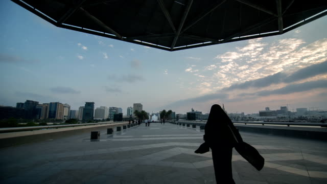 A woman in a flowing abaya walks at the Boulevard from the Museum of Islamic Art in Doha, Qatar