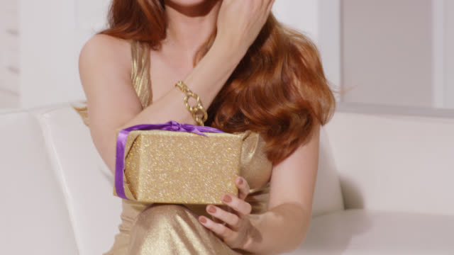 Woman in a gold glamorous dress and wavy red hair smiling and happy with her present
