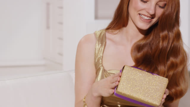Woman in a gold glamorous dress with wavy red hair holding a sparkly present box