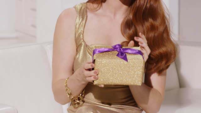 Woman in a gold glamorous dress with wavy red hair holding a sparkly present box with surprised expression