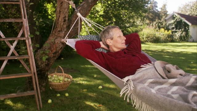 a woman in a hammock sweden. - hängmatta sol bildbanksvideor och videomaterial från bakom kulisserna