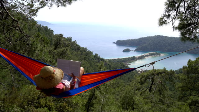 woman in a hammock with book on holiday - hammock stock videos & royalty-free footage