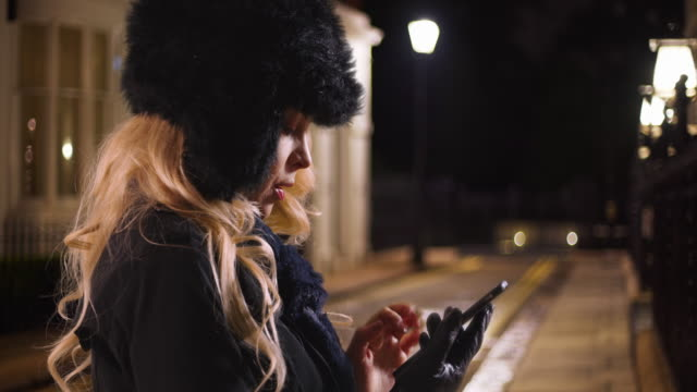 stockvideo's en b-roll-footage met woman in a hat and scarf types a message on her mobile phone at night - verdwaald