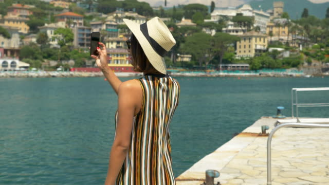 A woman in a hat takes pictures while traveling in a luxury resort town in Italy, Europe. - Slow Motion