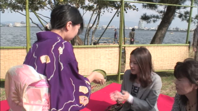 a woman in a kimono offers a bowl of tea to another woman in an outdoor tea ceremony. - tea party stock videos and b-roll footage