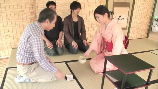 vidéos et rushes de a woman in a kimono serves a man a bowl of tea during a tea ceremony. - cérémonie