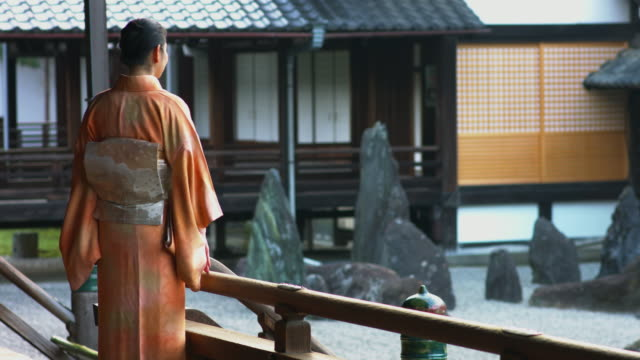 Woman in a kimono stood looking a rock garden