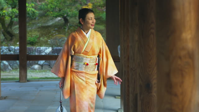 woman in a kimono stood pensively in a japanese temple - shrine stock videos & royalty-free footage