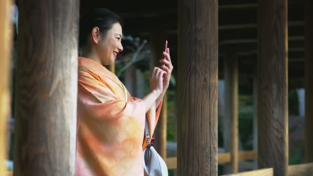 woman in a kimono taking a photo using her cell phone - kyoto temple stock videos and b-roll footage