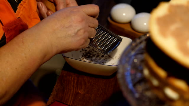 a woman in a kitchen apron rubs chocolate bar on a grater. - grater utensil stock videos & royalty-free footage