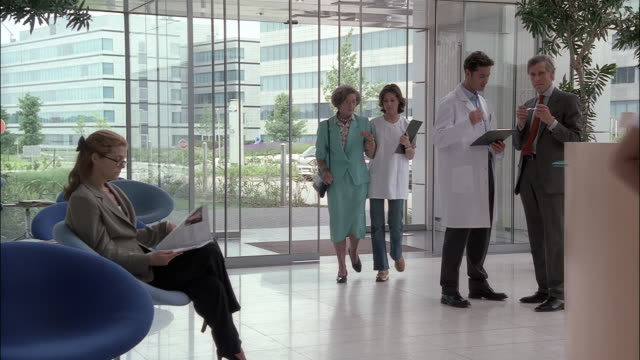stockvideo's en b-roll-footage met a woman in a lab coat assists a senior citizen patient. - lobby