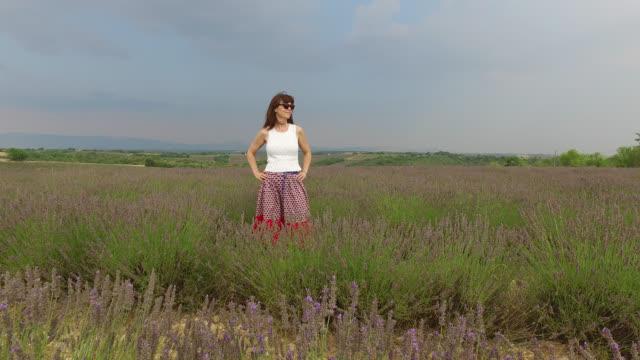 vidéos et rushes de woman in a lavender field in summer, provence, france - une seule femme d'âge mûr