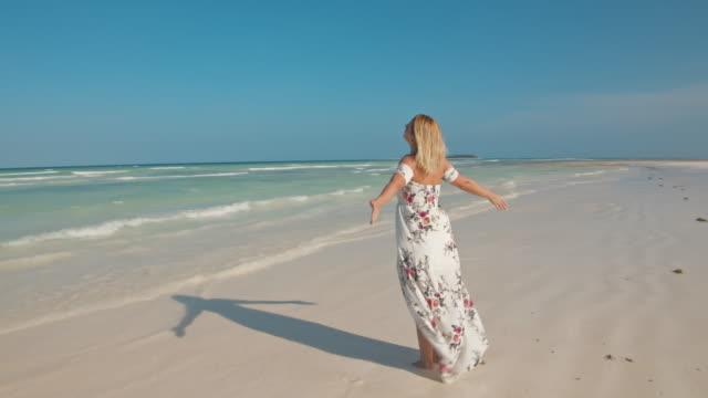 vidéos et rushes de slo mo femme dans une longue robe appréciant un air frais sur une plage de sable - robe