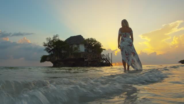 vidéos et rushes de femme de mo de slo dans une longue robe restant dans l'eau peu profonde sur une plage sablonneuse - robe