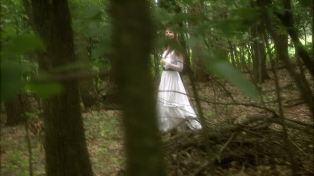 a woman in a long white dress with flowers in her hair walks through a forest. - vestito bianco video stock e b–roll
