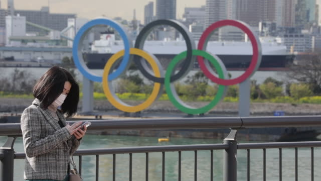 a woman in a mask looks at her phone in front of the olympic rings that are installed in the odaiba district of tokyo in minatoku on wednesday march... - japan bloomberg stock videos & royalty-free footage