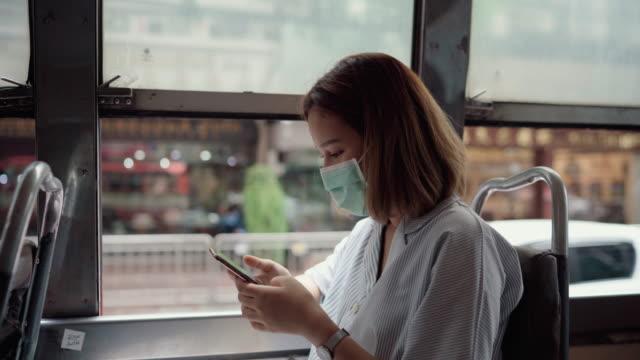 en kvinna i en mask i ansiktet på en buss till jobbet - thailändskt ursprung bildbanksvideor och videomaterial från bakom kulisserna