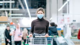 A woman in a medical mask stands in a supermarket with a grocery cart, timelapse. Protection from coronavirus, buying food in a crisis.