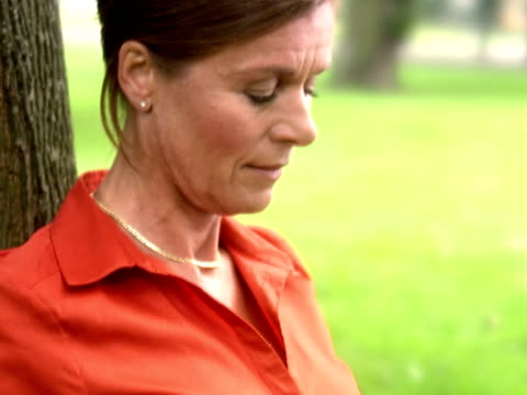 vídeos de stock, filmes e b-roll de a woman in a park using a laptop sweden. - só uma mulher madura