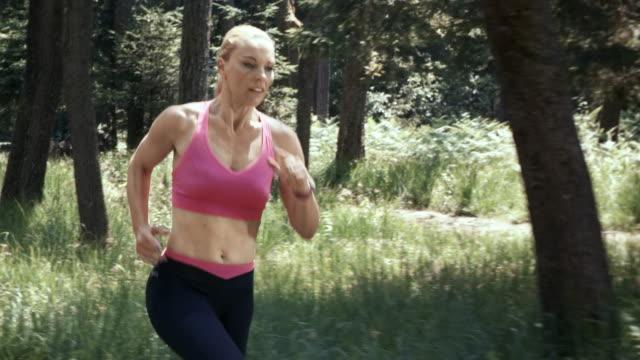 vídeos de stock, filmes e b-roll de slo mo ds mulher de camiseta rosa correndo na floresta - sutiã para esportes