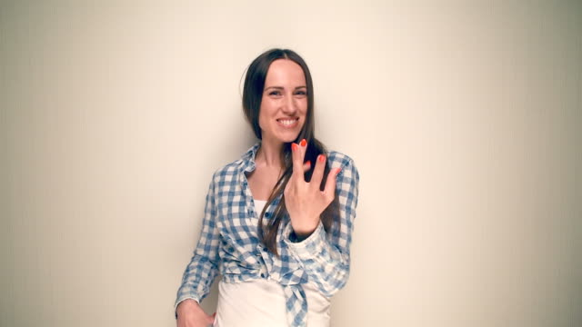 Woman in a plaid shirt pointing towards camera