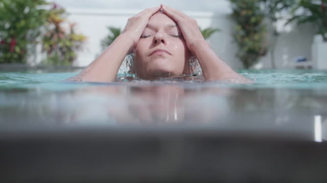 a woman in a pool ducking underwater at a resort hotel. - slow motion - zen like stock videos & royalty-free footage