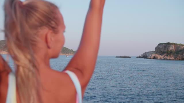 vidéos et rushes de woman in a rainbow swimsuit swimwear bikini on the bow of a sailboat boat while sailing in greece. - swimwear